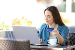 Kvinna som direktanslutet betalar med en b?rbar dator och en kreditkort i en st?ng arkivbild