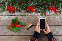 Kvinna som direktanslutet shoppar för jul på smartphonen Fotografering för Bildbyråer