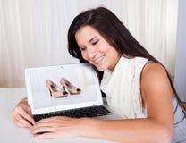 Kvinna som direktanslutet shoppar för skor Royaltyfria Bilder