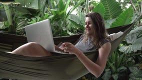 Kvinna som direktanslutet shoppar med kreditkorten och bärbara datorn, medan sitta på hängmattan stock video