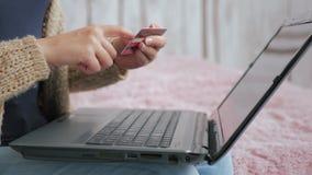 Kvinna som direktanslutet shoppar på bärbara datorn med kreditkorten Arkivfoto