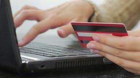 Kvinna som direktanslutet shoppar på bärbara datorn med kreditkorten Arkivbilder