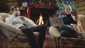 Kvinna som direktanslutet shoppar på bärbara datorn, medan mannen dricker kaffe under julafton lager videofilmer