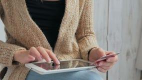 Kvinna som direktanslutet shoppar på den digitala minnestavlan med kreditkorten Fotografering för Bildbyråer