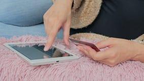 Kvinna som direktanslutet shoppar på den digitala minnestavlan med kreditkorten Royaltyfri Bild