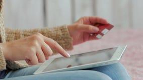 Kvinna som direktanslutet shoppar på den digitala minnestavlan med kreditkorten Arkivfoto
