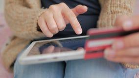 Kvinna som direktanslutet shoppar på den digitala minnestavlan med kreditkorten Royaltyfri Fotografi