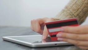 Kvinna som direktanslutet shoppar på den digitala minnestavlan med kreditkorten Royaltyfri Foto