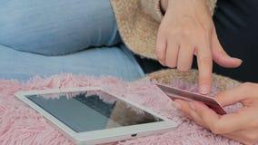Kvinna som direktanslutet shoppar på den digitala minnestavlan med kreditkorten Arkivbild