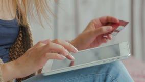 Kvinna som direktanslutet shoppar på den digitala minnestavlan med kreditkorten Arkivbilder