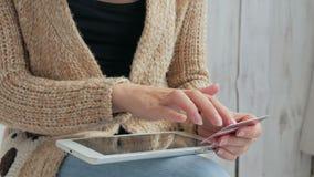 Kvinna som direktanslutet shoppar på den digitala minnestavlan med kreditkorten Royaltyfria Bilder