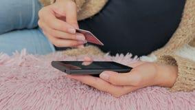 Kvinna som direktanslutet shoppar på smartphonen med kreditkorten Arkivfoton
