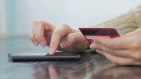 Kvinna som direktanslutet shoppar på smartphonen med kreditkorten Arkivbilder