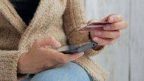 Kvinna som direktanslutet shoppar på smartphonen med kreditkorten Arkivfoto