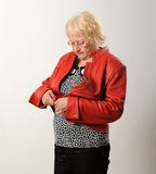 Kvinna som drar igen blixtlåset på det röda omslaget. Arkivbilder