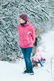 Kvinna som drar pulkan med hennes lilla dotter Royaltyfri Fotografi