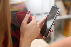 Kvinna som dricker coffe och blick p? b?rbara datorn royaltyfria foton