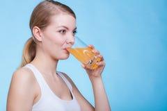 Kvinna som dricker den apelsin smaksatt drinken eller fruktsaft fotografering för bildbyråer