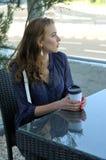 Kvinna som dricker drycken på ett utomhus- kafé royaltyfria bilder