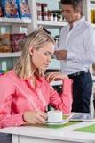 Kvinna som dricker ett kaffe arkivfoto
