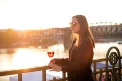 Kvinna som dricker ett vin i staden under en solnedgång glass rött vin Begrepp av fri tid i staden och drickaalkoholen royaltyfri bild