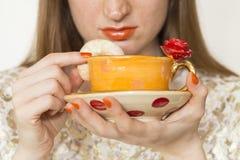 Kvinna som dricker från en härlig handgjord orange kopp Royaltyfri Foto