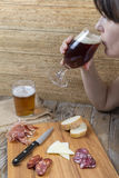 Kvinna som dricker från ett exponeringsglas av öl Royaltyfria Bilder