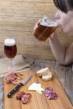 Kvinna som dricker från ett exponeringsglas av öl Royaltyfri Fotografi
