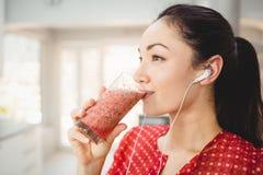 Kvinna som dricker fruktfruktsaft, medan lyssna till musik Arkivfoto