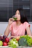 Kvinna som dricker grönsakfruktsaft i kök royaltyfri foto