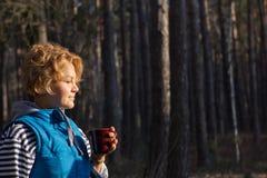Kvinna som dricker kaffe eller te som är utomhus- i ljust tycka om för sol Royaltyfri Bild