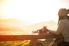 Kvinna som dricker kaffe, i att sitta för sol som är utomhus- arkivbild