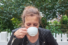 Kvinna som dricker kaffe i en trädgård royaltyfria bilder