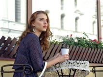 Kvinna som dricker kaffe i ett utomhus- kafé royaltyfri bild