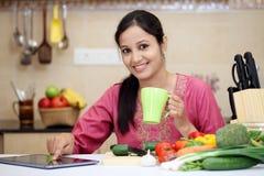 Kvinna som dricker kaffe i hennes kök Royaltyfria Bilder