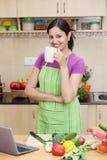 Kvinna som dricker kaffe i hennes kök Arkivfoton