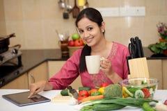 Kvinna som dricker kaffe i hennes kök Arkivbilder
