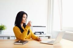 Kvinna som dricker kaffe i kontoret royaltyfria foton