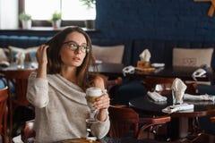 Kvinna som dricker kaffe i morgonen på den mjuka fokusen för restaurang på ögonen Royaltyfria Bilder