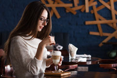 Kvinna som dricker kaffe i morgonen på den mjuka fokusen för restaurang på ögonen Royaltyfri Fotografi