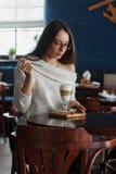 Kvinna som dricker kaffe i morgonen på den mjuka fokusen för restaurang på ögonen Arkivbild