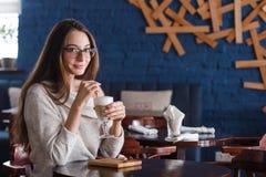 Kvinna som dricker kaffe i morgonen på den mjuka fokusen för restaurang på ögonen Arkivfoton