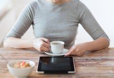 Kvinna som dricker kaffe och använder minnestavlaPC arkivfoton