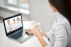 Kvinna som dricker kaffe och har videokonferens arkivfoto