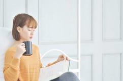 Kvinna som dricker kaffe och lästa böcker arkivfoto