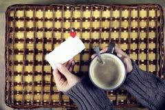 Kvinna som dricker kaffe och ser dagen för kortvalentin` s Arkivfoton