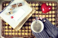 Kvinna som dricker kaffe och ser dagen för kortvalentin` s Royaltyfri Foto