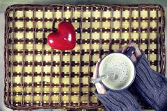 Kvinna som dricker kaffe och ser dagen för kortvalentin` s Arkivbild