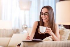 Kvinna som dricker kaffe och tar anmärkningar Royaltyfria Bilder