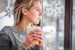 Kvinna som dricker kaffe och ut ser fönstret Royaltyfri Bild